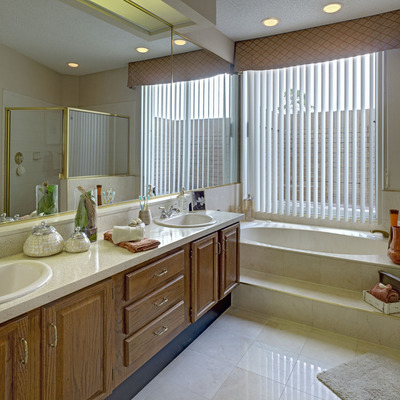 Whirlpool master bath with separate glass-enclosed shower and marble tile